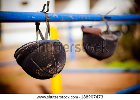 Riding helmet hanging from the metal fence - stock photo