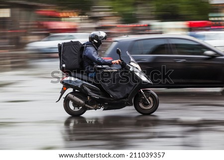 riding scooter in the rainy city - stock photo