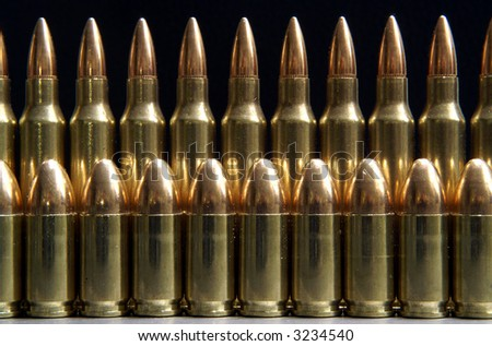 rifle and handgun bullets lined up in a row - stock photo