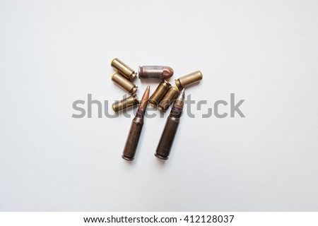 Rifle and pistol bullets on white background - stock photo