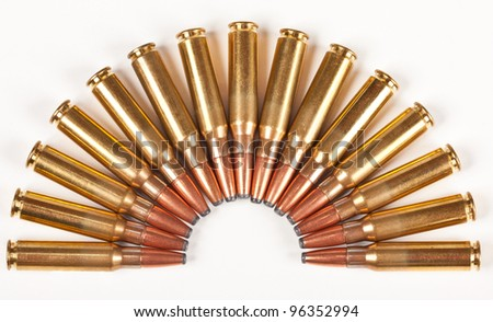 Rifle bullets packed in a half circle placed on a white surface - stock photo