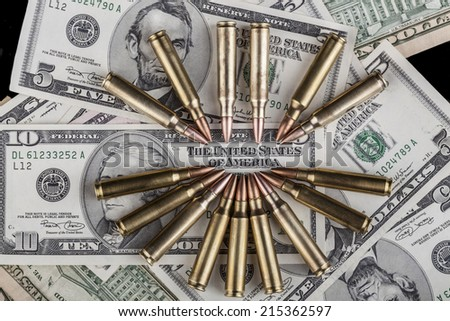 Rifle Bullets pointing at the United States text on a dollar banknote - stock photo