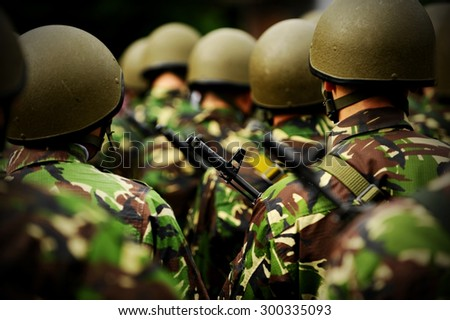 Rifle detail shot in a group of unrecognizable soldiers in camouflage uniform - stock photo