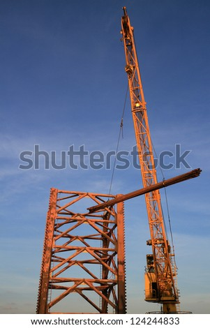 Rig Crane Lifts A Bundle of Drill Pipe To The Drilling Jack Up Rig - stock photo