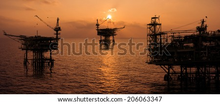 rig platform silhouette in oil and gas industry when sunset - stock photo