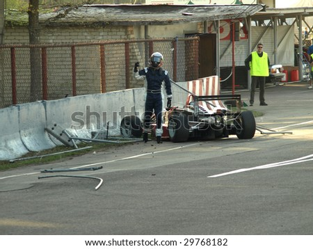RIGA, LATIVA - MAY 2: Formula 3 racing car Crash during Baltic Touring Car Championship. Driver Jani Tammi right after the collision shows that he is OK. May 2, 2009 in Riga, Latvia - stock photo