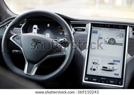 RIGA, LATVIA - DECEMBER 1, 2015: The interior of a Tesla Model S electric car with its large touchscreen dashboard. - stock photo