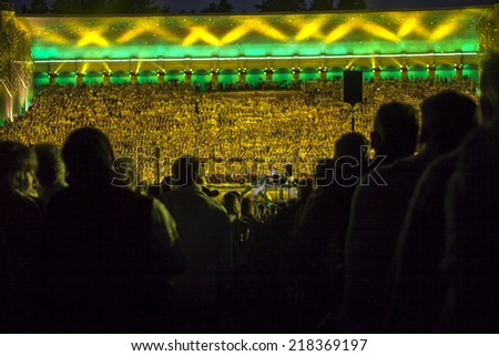"RIGA, LATVIA - July 7, 2013: The Latvian National Song and Dance Festival Grand Finale concert ""Ligo!"". View on  mass choir from spectator seats. - stock photo"