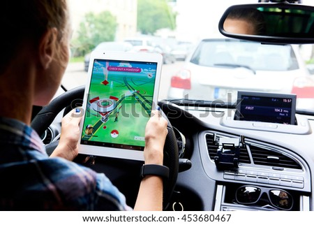 Riga, Latvia- July 17, 2016: Woman sitting in a car and playing a Pokemon Go game. Pokemon Go is a popular virtual reality game for mobile devices - stock photo