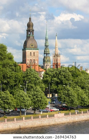 RIGA, LATVIA - JUNE 17, 2008: View on the towers of Riga Cathedral, St Peters Church and the English Church in Riga, Latvia, by the river Daugava. - stock photo