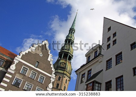 RIGA, LATVIA - MARCH 19, 2012: St. Peter's church in Riga with neighboring houses - stock photo