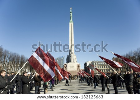 "RIGA, LATVIA-MARCH 16:The Latvian hawks of with flags before procession of legionaries  ""Waffen SS"" to Freedom monument. Riga, Day of memory of legionaries of ""Waffen SS"" in March 16, 2013 in Riga. - stock photo"