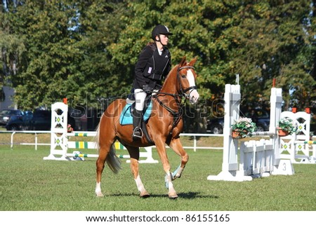 RIGA, LATVIA - SEPTEMBER 25 : An unidentified child on pony show jumps during Latvian Equestrian Federation cup in pony riding on September 25, 2011 in Riga, Latvia. - stock photo