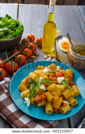 Rigatoni pasta with mozzarella and tomato, fresh herbs on top, very simple and delicious meal - stock photo