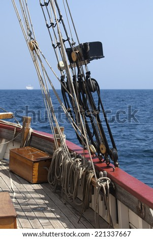 Rigging of a tall ship against blue sky and sea - stock photo