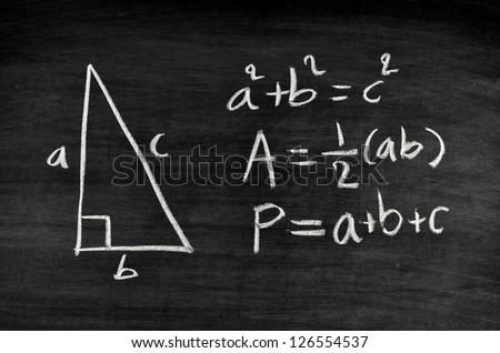right-angled triangle area and perimeter formula written on blackboard - stock photo