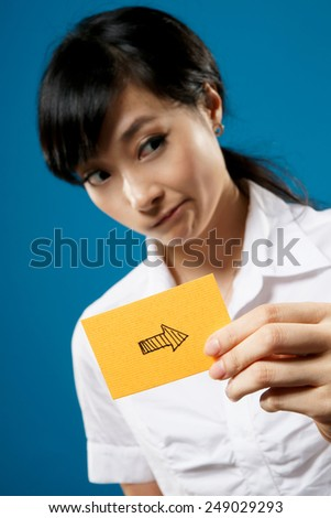 Right arrow on business card holding by Asian businesswoman on studio blue background. - stock photo