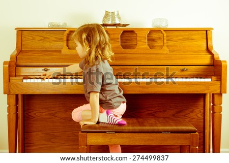 Right note requires effort outside your comfort zone in a conceptual image with a little girl climbing on the stool to stretch across a piano keyboard for the correct key or note - stock photo