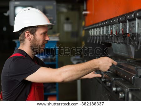 right side close-up of a worker, wearing red overalls, and a white protective helmet assisting an industrial machinery, painted in red and black, with a control panel in the background - stock photo