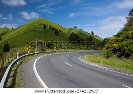 Right Turn. Empty winding roadway in countryside of Awakino, New Zealand on sunny day. - stock photo