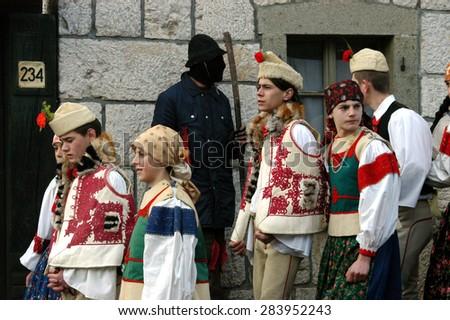 RIMETEA - FEB 28: Local unidentified villagers of Torocko attending the carnival show, the celebration at the ending of winter. On February 28, 2004 in Rimetea, Romania                                 - stock photo