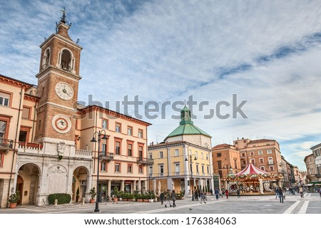 RIMINI, ITALY - FEBRUARY 7: people walking in the square Piazza tre Martiri with the ancient clock tower, the church and an old horse carousel, on February 7, 2014 in the old town of Rimini, Italy  - stock photo