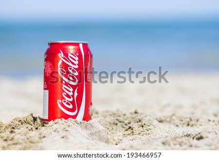 Rimini,Rivazzurra,IT. May 18,2014.Coca cola can on the beach.Coca-Cola is a carbonated soft drink sold in stores, restaurants, and vending machines throughout the world.  - stock photo