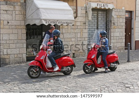 RIMINI - SEPTEMBER 17: Vespa scooters on the street of Rimini, on 17 September, 2012 in Rimini, Italy. Vespa is an Italian brand of scooter manufactured by Piaggio. The name means wasp in Italian. - stock photo