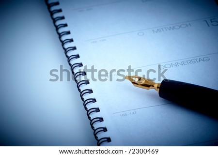 ring binder calendar with an old stylograph - stock photo