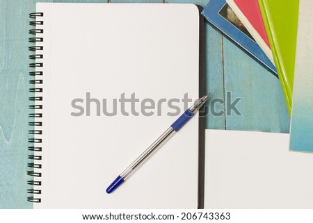 Ring binder, pen and a stack of books. Writing material ready to take notes, do homework or research. Directly above - stock photo