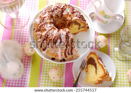 ring cake poured icing and chocolate sauce ,decorated with colorful sprinkles on easter table - stock photo