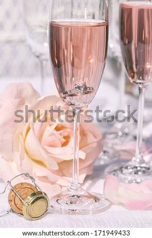 Ring in pink champagne with flowers - stock photo