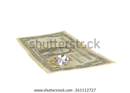 Ring on a $1 bill representing the high cost of weddings, isolated on white - stock photo