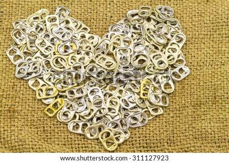 Ring pull aluminum of cans stack as heart shape indicate of new hope on brown sack fabric - stock photo