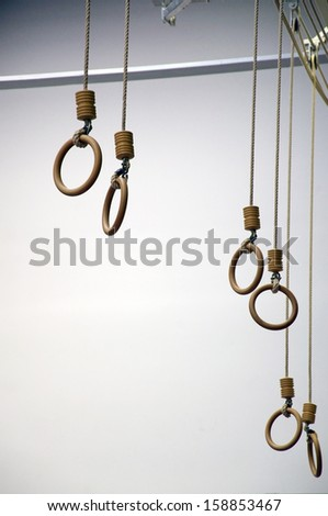 Rings in a gym, hanging from the ceiling - stock photo