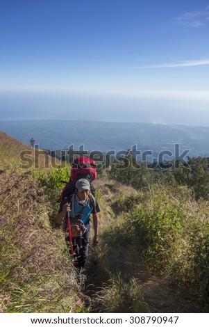 RINJANI MOUNTAIN, LOMBOK, INDONESIA-JUNE 11,2015: Mountain guide AB Pramono with trekking pole walks slowly on trekking path on the way to Rinjani Mountain in Lombok, Indonesia. - stock photo