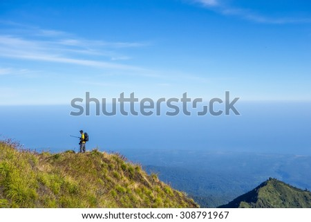 RINJANI MOUNTAIN, LOMBOK, INDONESIA-JUNE 11,2015: Unidentified hiker takes a dangerous selfie at 2,500m above sea level at Plawangan Senaru on his way to climb Rinjani Mountain in Lombok. - stock photo