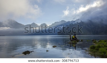 RINJANI MOUNTAIN, LOMBOK, INDONESIA-JUNE 11,2015: Unidentified local kids fish at Lake Segara Anak at  Rinjani Mountain in Lombok, Indonesia. - stock photo