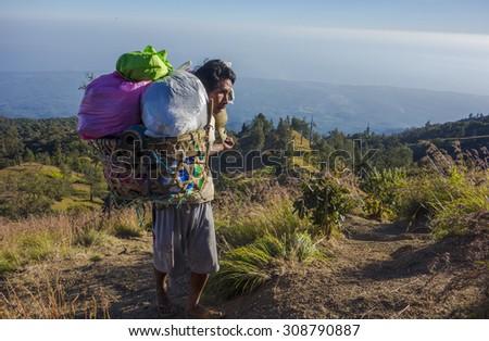 RINJANI MOUNTAIN, LOMBOK, INDONESIA-JUNE 11,2015: Unidentified mountain porter carries food necessities walks slowly on trekking path on the way to Rinjani Mountain in Lombok, Indonesia. - stock photo