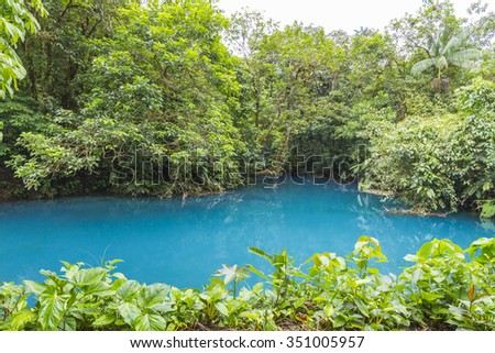 Rio Celeste, famous for it's blue colour due to dissolved salts from the Tenorio Volcano. It flows through forest on the flank of the volcano in Costa Rica - stock photo