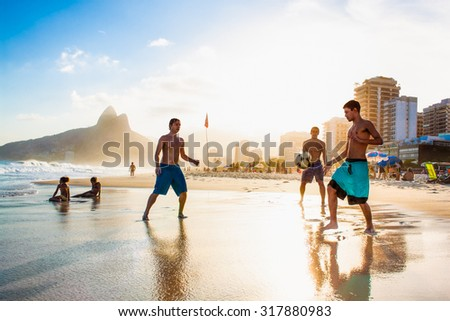 RIO DE JANEIRO, BRAZIL - APRIL 24, 2015: Carioca Brazilians playing altinho futebol beach football kicking soccer balls at sunset Ipanema Beach on April 24, 2015, Rio de Janeiro. Brazil. - stock photo