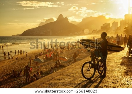 RIO DE JANEIRO, BRAZIL - APRIL 23, 2013: Silhouete of Brazilian surfer overlooking the ocean at Praia de Ipanema with Morro Dois Irmaos  and the sun setting in the background. - stock photo