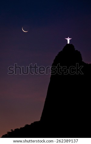 RIO DE JANEIRO, BRAZIL - DECEMBER 4, 2013: Spectacular view of illuminated Christ the Redeemer statue on the Corcovado Mountain at night with young moon in the sky. - stock photo