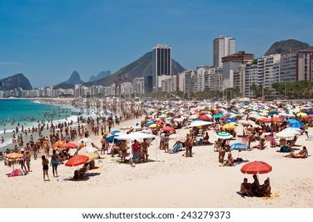 RIO DE JANEIRO, BRAZIL - DECEMBER 28, 2014: Thousands of brazilians and foreigners enjoy hot and sunny weekend in Copacabana beach. - stock photo