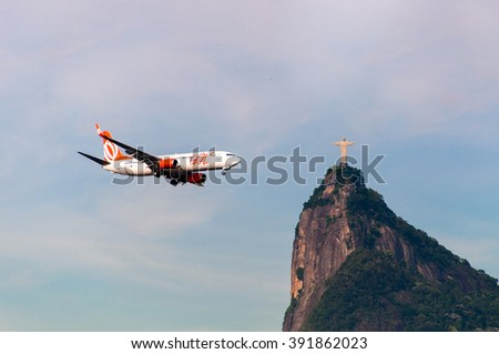 RIO DE JANEIRO, BRAZIL - FEBRUARY 26, 2016: Gol Airlines aircraft is flying towards the Christ the Redeemer statue on Corcovado mountain. - stock photo