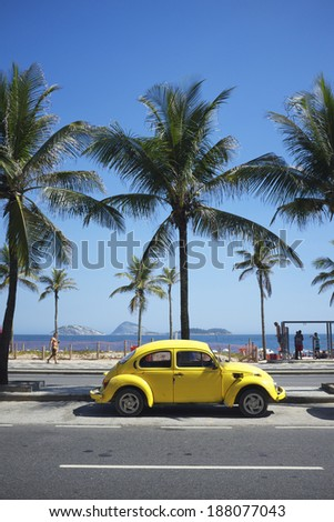 RIO DE JANEIRO, BRAZIL - FEBRUARY 6, 2014: Old yellow Volkswagen Type 1 Beetle, known locally as a Fusca, parked in front of Ipanema Beach. - stock photo
