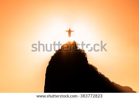 RIO DE JANEIRO, BRAZIL - FEBRUARY 2, 2016: Sun goes down right behind Christ the Redeemer statue on Corcovado mountain in Rio de Janeiro. - stock photo