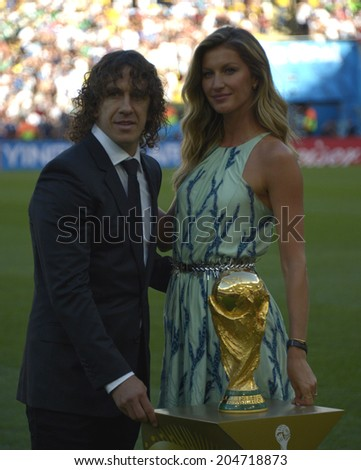 RIO DE JANEIRO, BRAZIL - July 13, 2014: Carles Puyol and Gisele Bundchen at the 2014 World Cup Final game between Argentina and Germany at Maracana Stadium. NO USE IN BRAZIL. - stock photo