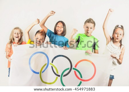 RIO DE JANEIRO, BRAZIL - JULY 17, 2016: Group of children holding a flag of five rings symbol of the Olympic Games. Rio de Janeiro 2016 Brazil. Happy fans of kids watching tv. Volunteer - stock photo