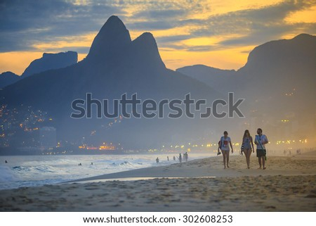RIO DE JANEIRO, BRAZIL - JULY 17: People relaxing on Ipanema Beach during beautiful  sunset on July 17, 2015. - stock photo